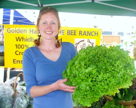 Soma, from Five Acre Farm in Coupeville, holding a head of lettuce that is not only as big as her head, it is as big as her entire torso! Photo copyright 2009 by Zachary D. Lyons.