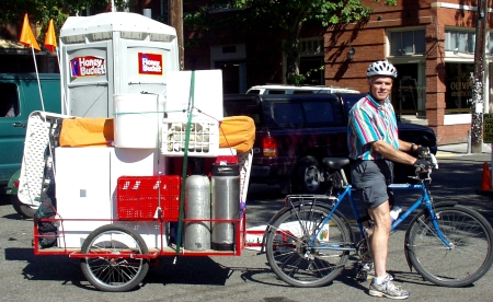 Communi-Tea Kombucha man, Chris Joyner, riding off from the Ballard Farmers Market with a bicycle trailer full of his display, and... is that a porta-potty? Photo copyright 2009 by Zachary D. Lyons.