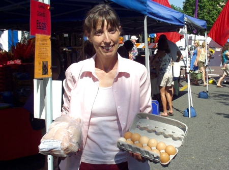 Janelle Stokesberry holding a chicken and a dozen eggs from Stokesberry Sustainable Farm in Olympia. Photo copyright 2009 by Zachary D. Lyons.