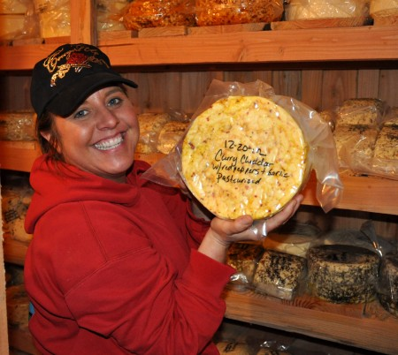 Cheese maker Heather Howell of Twin Oaks Creamery holds up a wheel of her flavored cheddar. Photo copyright 2013 by Zachary D. Lyons.